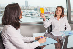 Warning from a boss. Boss giving the yellow card to a woman royalty free stock photos