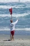 Warning danger. Lifeguard warning swimmers of danger waving red flag Royalty Free Stock Photos