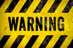 WARNING danger sign word text as stencil with yellow and black stripes painted over concrete wall cement texture background stock photography