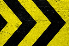 Warning danger sign yellow and black stripes as arrows painted over concrete cement wall as texture background. stock image
