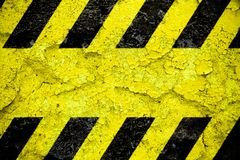 Warning danger sign yellow and black stripes pattern with yellow area over concrete cement wall facade peeling cracked Danger sign stock images