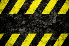 Warning danger sign yellow and black stripes pattern with black area over concrete cement wall facade peeling cracked paint. stock image