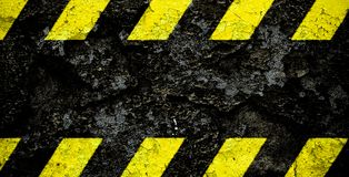 Warning danger sign yellow and black stripes pattern with black area over concrete cement wall facade peeling cracked paint. Wide panorama background do not royalty free stock photo