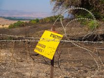 Warning of danger to life in Hebrew, English and Arabic. A warning sign about a minefield written in Hebrew, Arabic and English, fenced with barbed wire Royalty Free Stock Photography