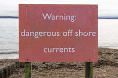 Warning dangerous off shore currents sign. Red notice on UK beach warning of currents at sea Stock Photos