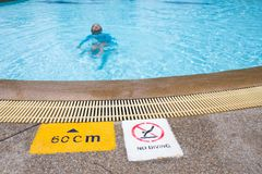 Warning and depth sign at swimming pool for children with blurre. D kid swimming in background Stock Images