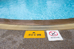 Warning and depth sign at swimming pool for children. Warning and depth sign at clean and clear water swimming pool for children with copy space Royalty Free Stock Image