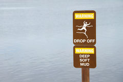 Warning drop off sign near cliff by waters edge Stock Photo