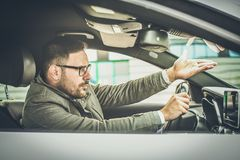 Warning are everywhere. Enraged male driver shouts and gestures threateningly. Close up royalty free stock image
