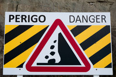 Warning for falling rock stones. A metal board with a warning sign for falling rock stones with the word Danger and Perigo (Portuguese for danger) on it Royalty Free Stock Image
