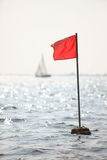 Warning flag. Red diving flag floating on a buoy Royalty Free Stock Photography