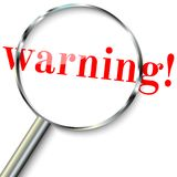 Warning in focus. Steel Magnifying glass Concept - warning. For websites, blogs Royalty Free Stock Photos