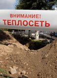 The warning inscription `Attention to the heating network` before the excavated trench stock image