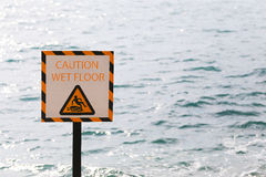 Warning labels of Caution wet floor in seaside area. Stock Images