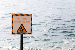 Warning labels of warning beware slippery in seaside area. Royalty Free Stock Photography