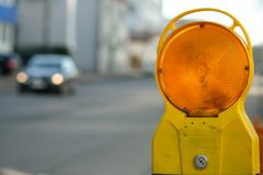 Warning light at a construction in road traffic. With blurred car Royalty Free Stock Images