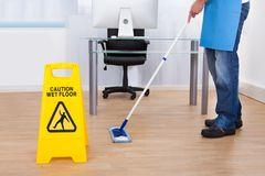 Warning notice as a janitor mops the floor. Yellow warning notice to caution people to a slippery wet surface as a janitor mops the floor in an office building Royalty Free Stock Images