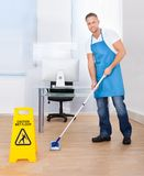 Warning notice as a janitor mops the floor. Yellow warning notice to caution people to a slippery wet surface as a janitor mops the floor in an office building Royalty Free Stock Photo