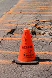 Warning - Orange Cone. An orange cone and painted concrete warn of a set of cracks in the tarmac at an airport stock photography