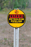Warning Petrolium Pipeline Sign. A red, black and yellow sign on a post reading Warning Petrolium Pipeline against a natural background Royalty Free Stock Images