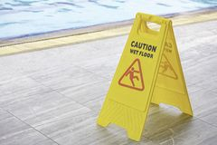 Warning plates wet floor beside the pool stock photos