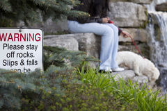 Warning, Please stay off rocks. A lady and her dog ignoring a warnign sign Stock Images