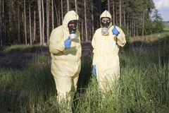 Warning about radiation in forest. Two experts checking field for radiation royalty free stock photos