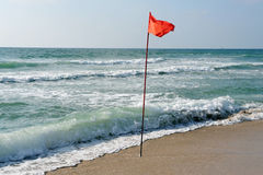 A warning Red flag of danger at sea Stock Photo