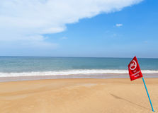 Warning red flag no swimming sign on the beach Royalty Free Stock Photography