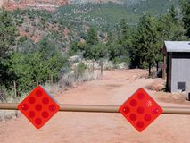 Warning red reflector signs hanging on the blocking way barrier Stock Photos