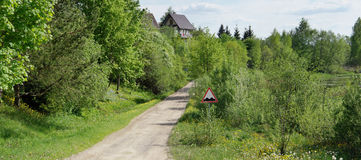 The warning road sign. `Bumpy road` stands on the way to the forest European village. Sunny spring day panoramic landscape Royalty Free Stock Photos