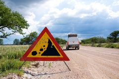 Warning of road sign - falling stones on the road Royalty Free Stock Photography