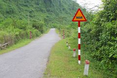 Warning road sign floods jungle mountains, Phong Nha, Vietnam royalty free stock images