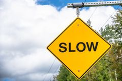 Warning Road Sign Saying `Slow`. Hanging Yellow Warning Road Sign Reading `Slow` along a Country Road on a Cloudy Summer Day. British Columbia, Canada stock photos
