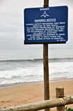 Warning sign. A warning notice of sharks in the area, with surfer in backgrounnd Royalty Free Stock Photo