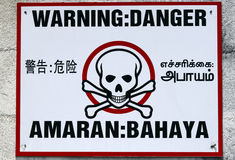Warning sign. A warning sign in four languages, English, Mandarin, Tamil & Malay stock photos