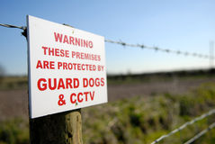 Warning sign. Red letters on a warning sign to protect premises/land nailed to a wooden post on fence Stock Photo