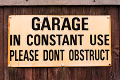 Warning sign. A sign with the words Garage in constant use please do not obstruct requesting that vehicle drivers do not park blocking the entrance and exit to a stock photography