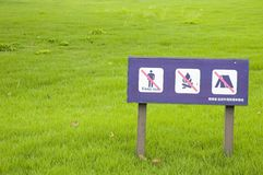 Warning Sign. Close up shot of a warning sign on Grass, Tokyo, Japan Royalty Free Stock Photo