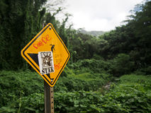 Warning sign along a hiking trail in Hawaii with grafitti. A warning sign on a hiking trail in Hawaii has been defaced with defiant grafitti Royalty Free Stock Photos