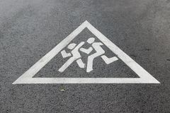 Warning sign `Attention, children!` painted on the road. As a background stock image