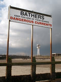 Warning sign on a beach and lighthouse Stock Images