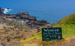 Warning Sign Blowhole Maui. Tourist warned to stay clear of the blow hole at the cliffs edge. Dangerous and could cause injury or death. Despite warning, notice stock images