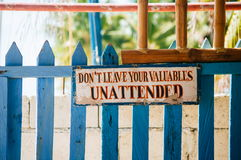 Warning sign board hanging on the wooden gate: Don`t leave you valuables Unattended.  Royalty Free Stock Images