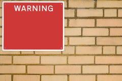 Warning sign on brick wall. Stock Photo