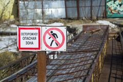 Warning sign `caution. danger zone ` in Russian. Emergency bridge in the background. Close-up-image stock photo