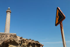 Warning sign by cliff fall. Warning Sign fall by cliff, next to a lighthouse Stock Photo