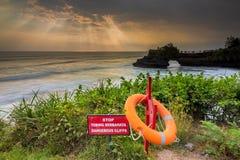 Warning Sign at a cliff and ray of lights at pura batu bolong, b Royalty Free Stock Images