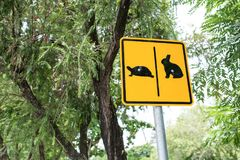Warning sign cross the road rabbit and turtle in park. Warning sign cross the road rabbit and turtle in public park stock photos