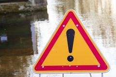warning sign of danger in front of a flooded road Stock Photo